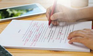 Hand proofreading text using a red pen