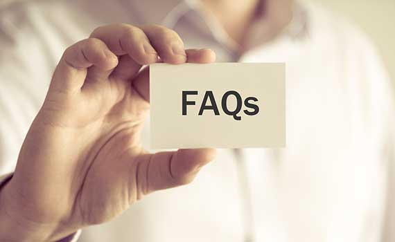Person holding a white card with 'FAQs' text