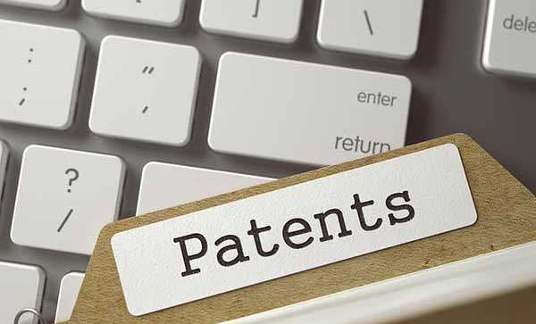 File card labeled Patents on top of a computer keyboard